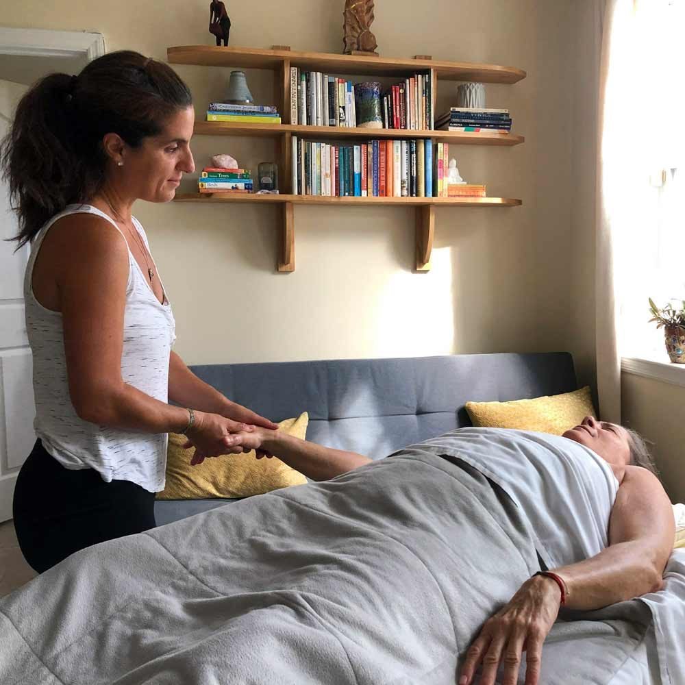 Dana working with massage client in their homel.